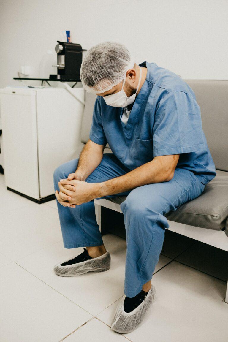 Pfleger sitzt mit dem Oberkörper nach vorne gebeugt