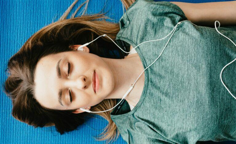 Frau liegt auf Sportmatte und hört Musik über Kopfhörer