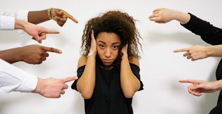 Frau hält sich Hände an Kopf während viele Hände auf sie zeigen